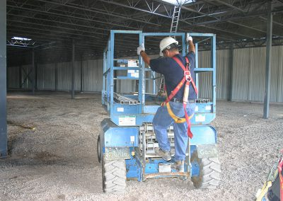 worker climbing onto electric scissor lift