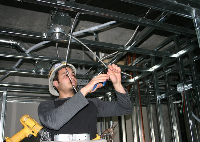 electrical worker connecting ceiling wiring