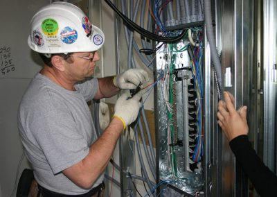 electrical worker connecting wires to fuse panel