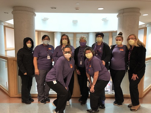 workers posing in medical masks during COVID crisis